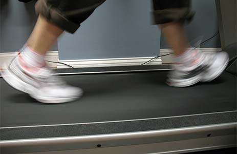 Woman working at a treadmill desk.